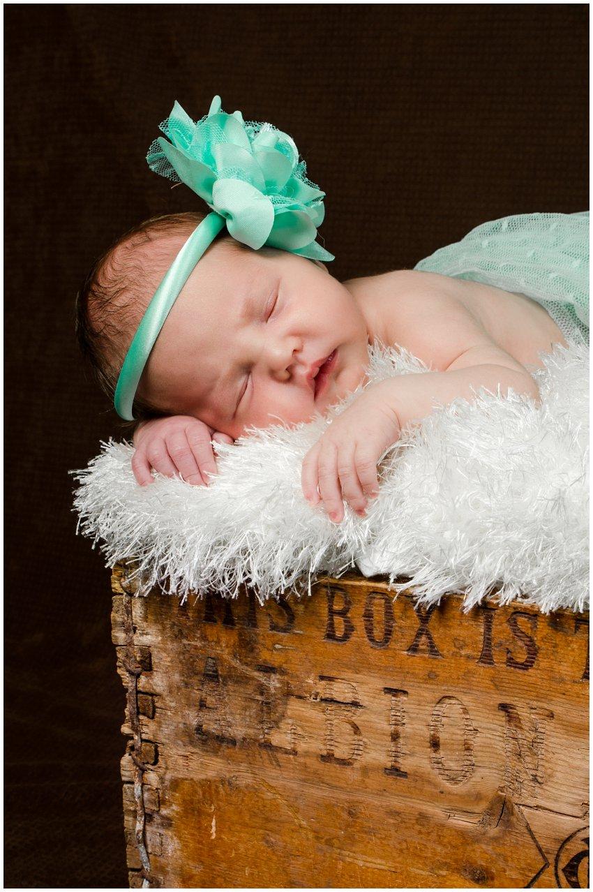 Newborn baby girl in mint green