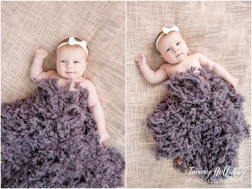 baby wearing bow on head covered in ruffled purple blanket lying on brown backing