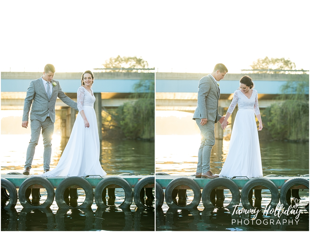 bride and groom pose by water standing