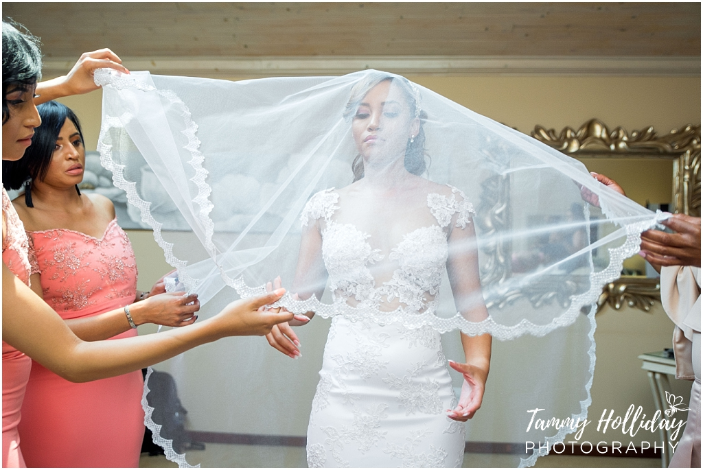 Bridesmaids helping place veil on head