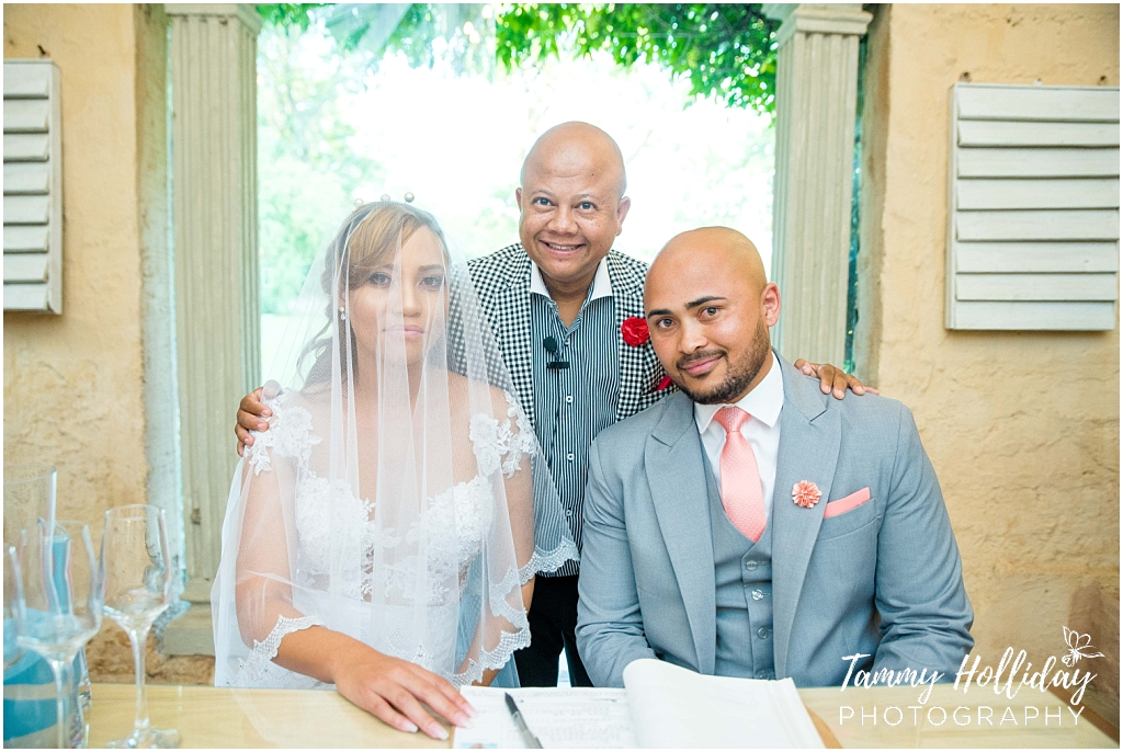 bride and groom with pastor with marriage contract