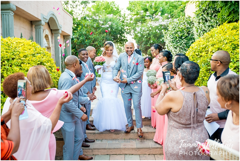 bride and groom petal toss guests and garden background
