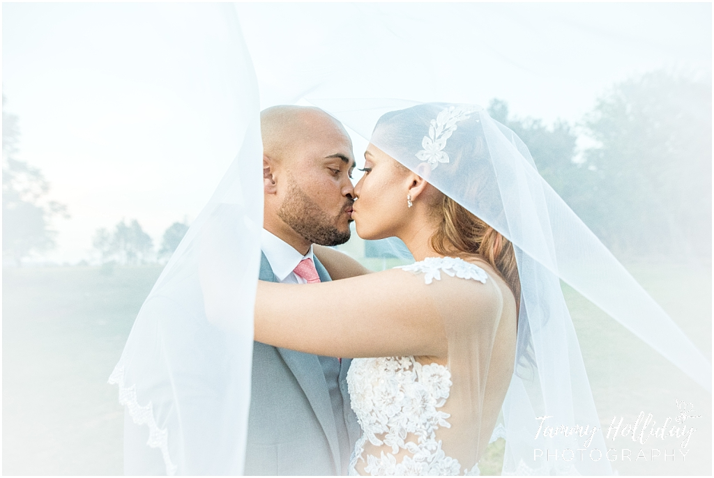 bride ad groom kissing under veil