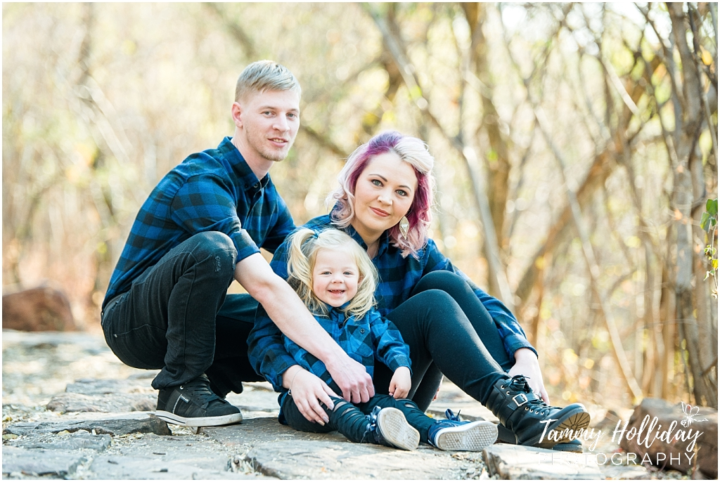 mom dad and daughter family phot on rock wearing black jeans blue and black checkered shirts