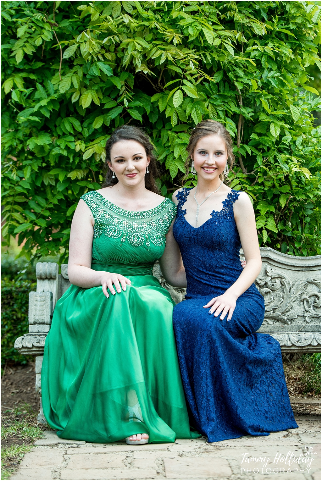 matric girl in green dress sitting on concrete bench with friend in a blue dress