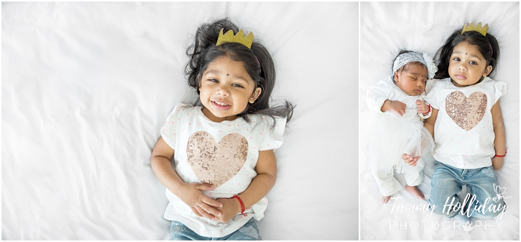 little girl lying on white bedding wearing white t-shirt with gold heart on wearing crown headband on head