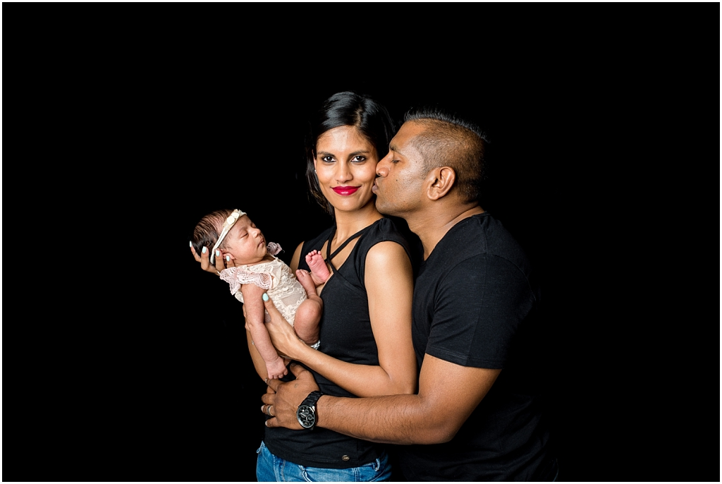 mom and dad holding baby girl wearing black tops and blue jeans baby wearing lace outfit with headband family photography family photoshoot new born photoshoot