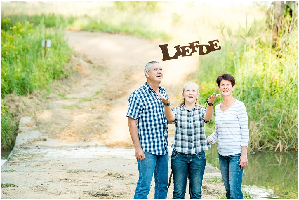 family of three throwing liefde sign up in air modderfontein nature reserve family photoshoot nature photoshoot family photographer dirt road long green grass location photography