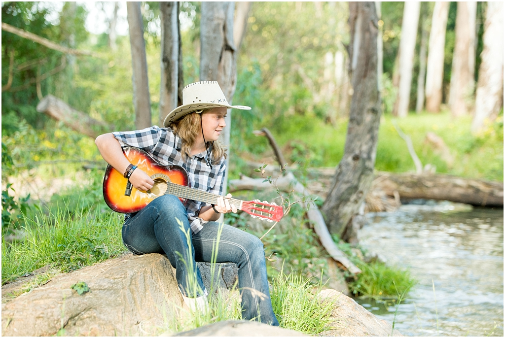 girl wearing cowboy hat playing guitar by stream wearing blue checkered shirt sitting on rock modderfontein nature reserve family photoshoot family photography family in nature photoshoot