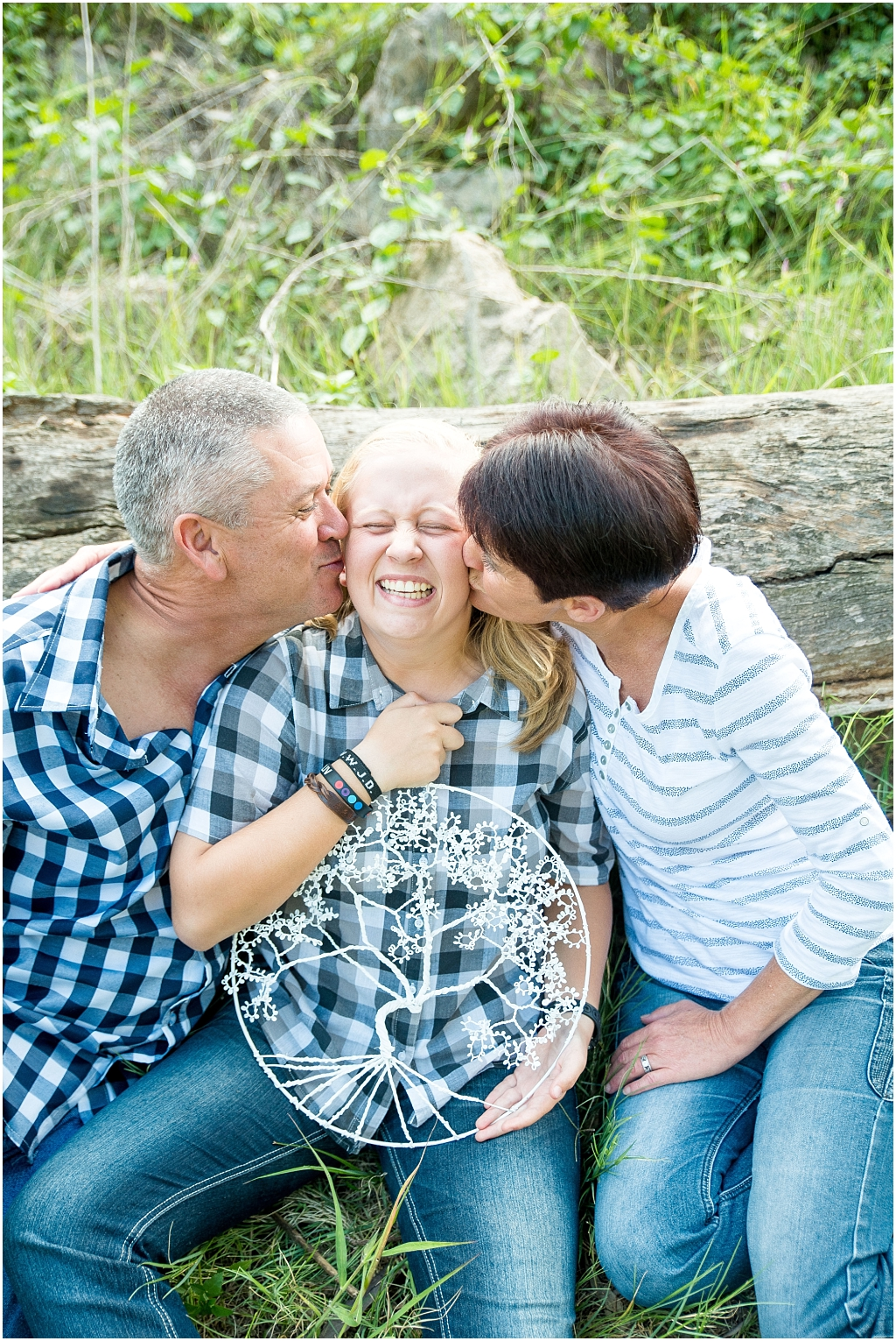 parents kissing daughter on cheek holding family tree sitting against fallen tree family photographer family photo shoot modderfontein nature reserve
