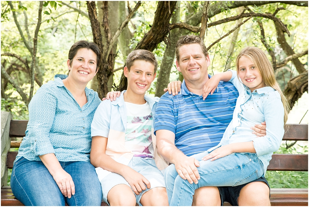 happy family photoshoot mom dad brother sister sitting on park bench wearing light blue colours