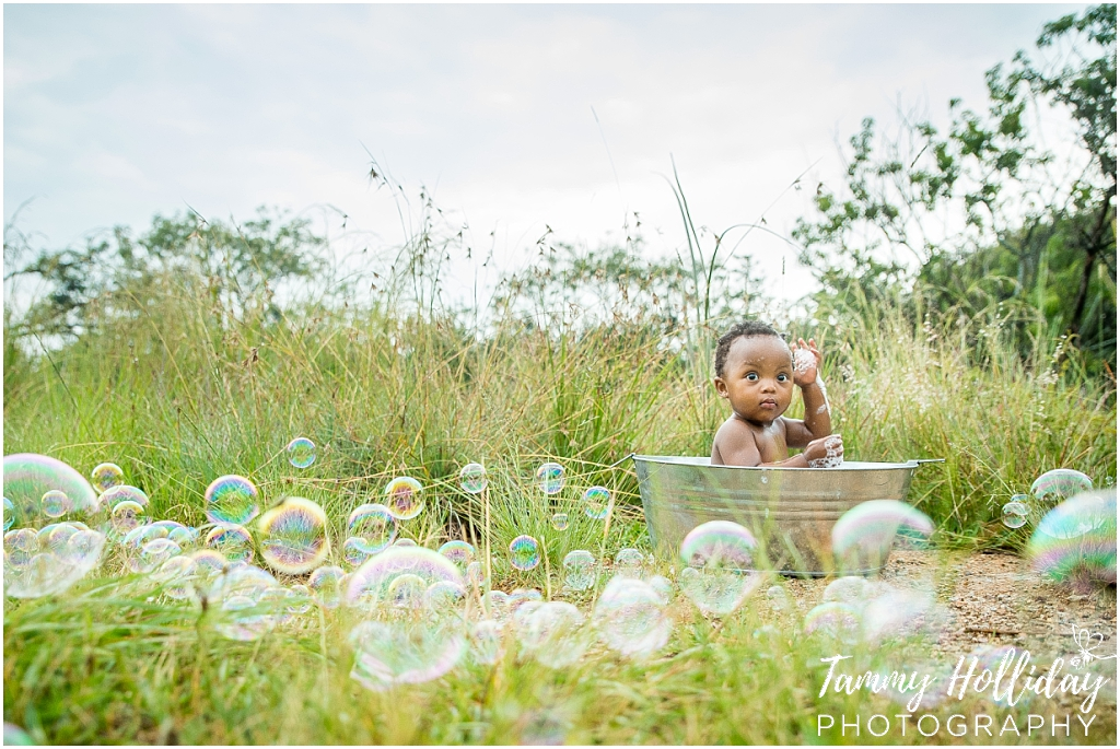 little girl sitting in steel bath outdoors with bubbles
