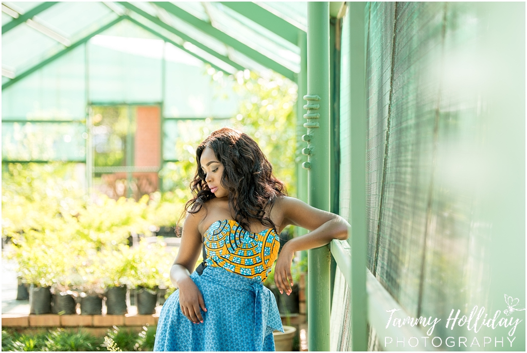 portrait photo shoot lady standing in greenhouse wearing blue dress with gold top