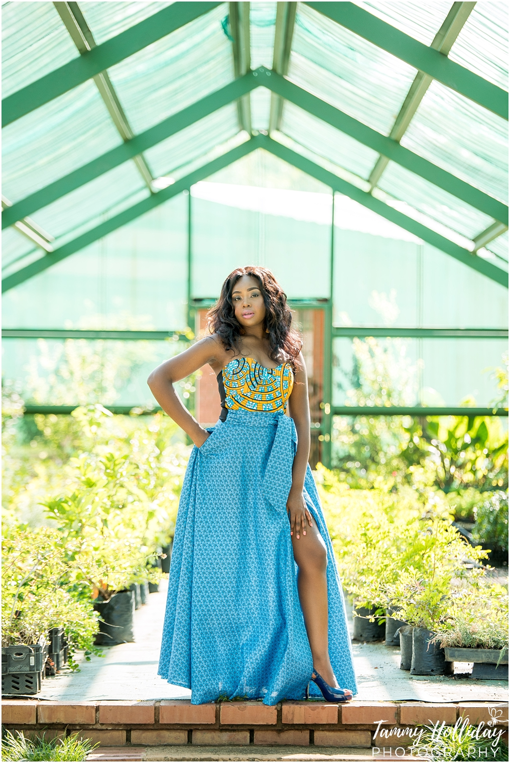 striking a pose in a greenhouse full of greenery wearing blue dress with slit portfolio shoot