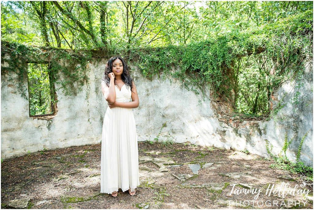 lady standing outside by abandoned building wall filled with growing greenery wearing a white dress portfolio shoot