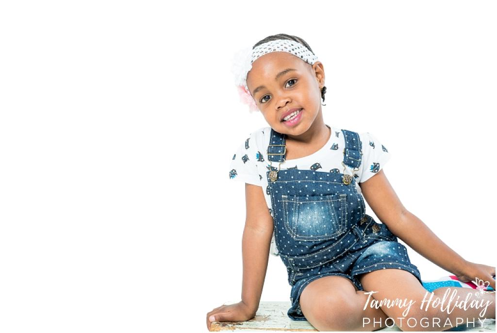 little girl sitting on floor smiling wearing blue denim with white background studio shoot family photo shoot