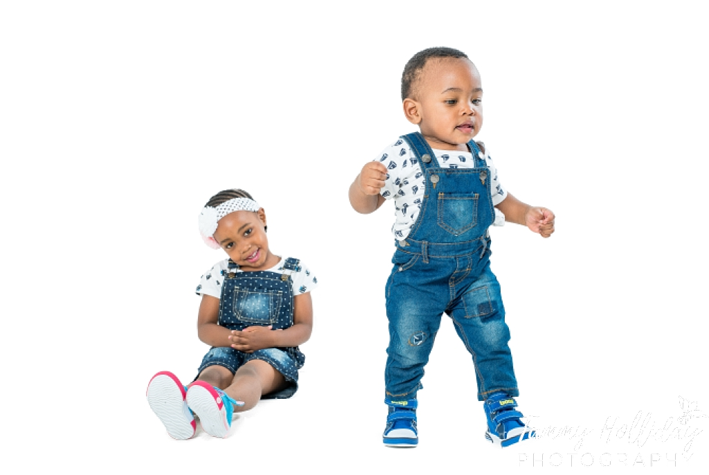 brother and sister in studio shoot wearing blue denim dungarees with little boy walking away and little girl sitting smiling sibling photos