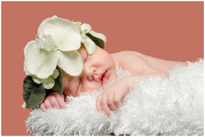 Newborn baby girl with flowers on head