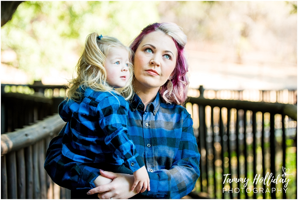 mom holding daughter wearing blue and black checkered shirts
