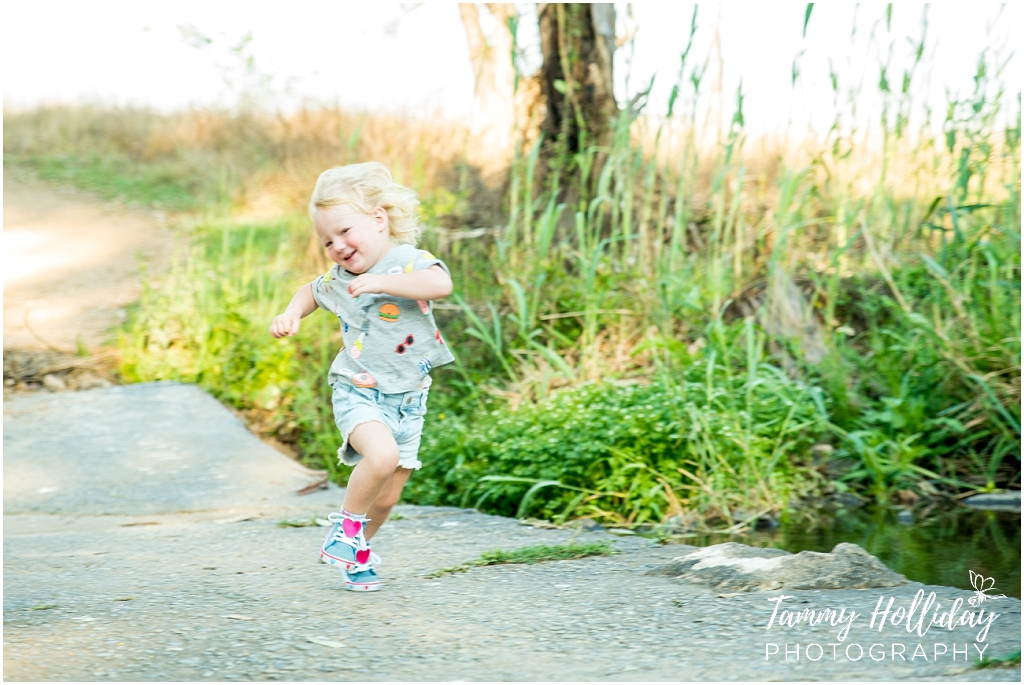 little girl running on paved ground with greenery background