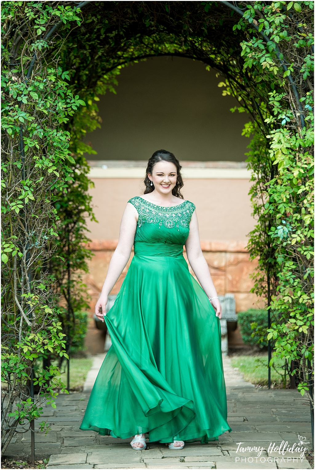 Teenager dressed in green dress standing in greenery arch