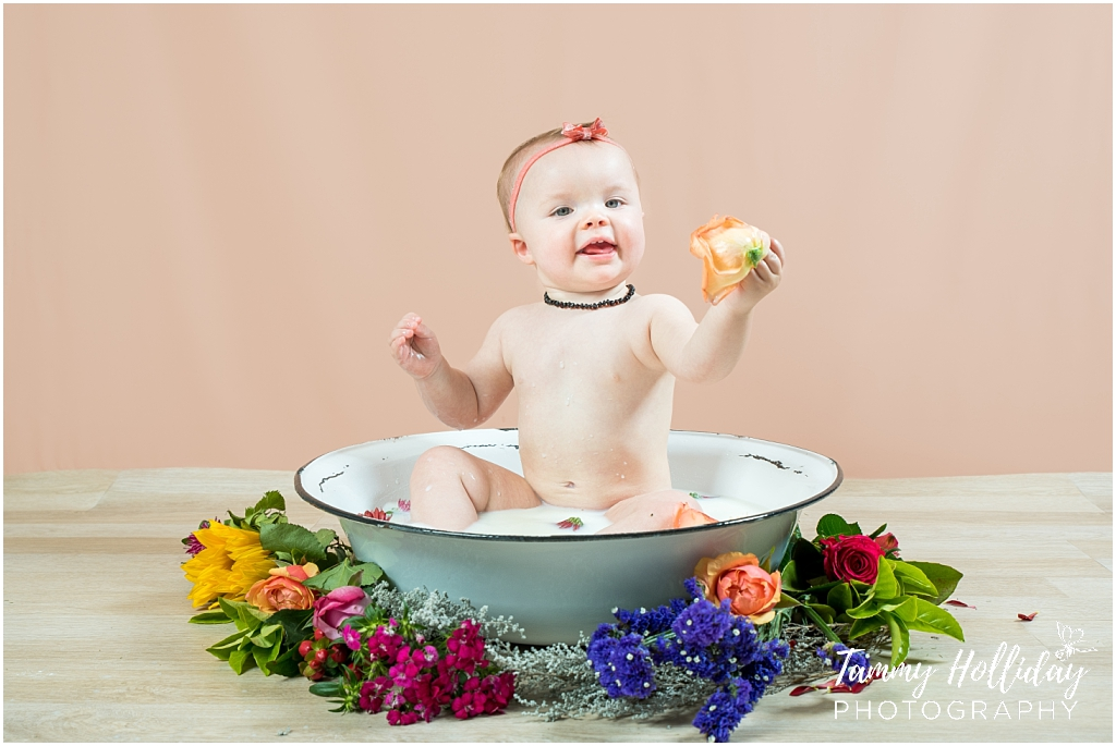 child in old steel bath surrounded by flowers with pink backdrop