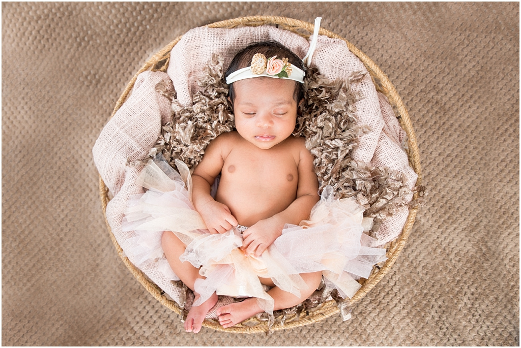 new born baby girl lying in woven basket brown background with headband on head