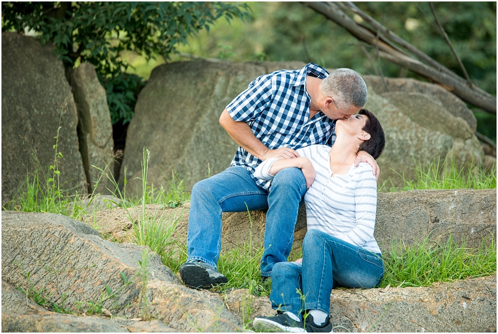 parents in love sitting on rock kissing family in nature photoshoot family photography location photoshoot