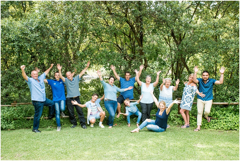 big happy family photoshoot celebrating in park with greenery around wearing light blue