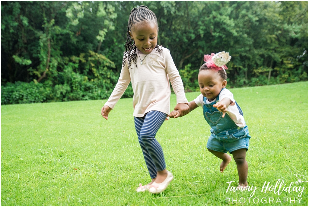 little sisters holding hands walking in grass park family photographer