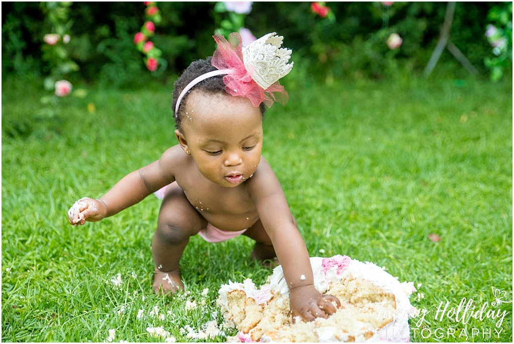 cake smash photo shoot on location little girl smashing pink cake wearing pink crown headband smashing cake