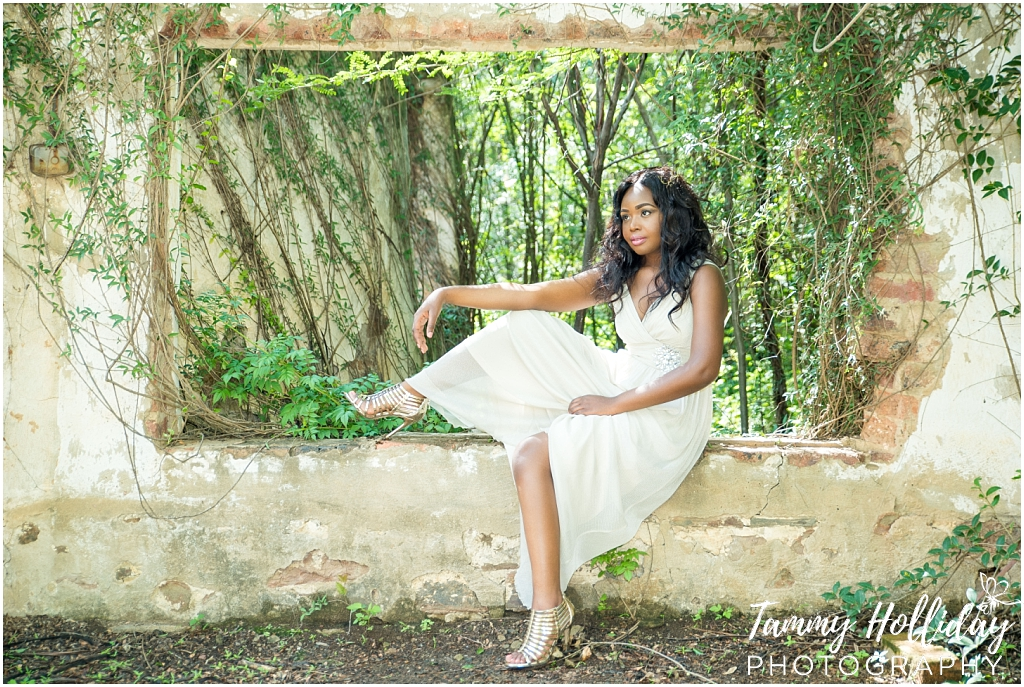 lady sitting in old window surrounded by greenery wearing white dress and gold shoes portfolio shoot